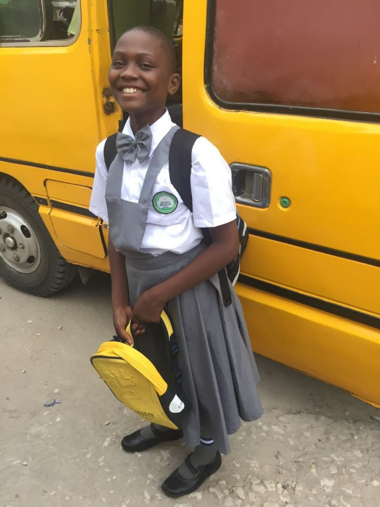 Girl in school uniform standing in front of school bus